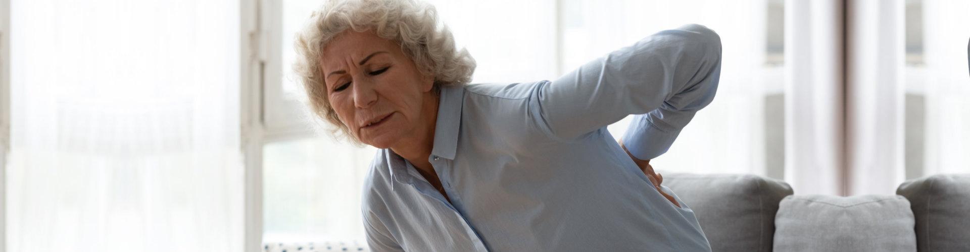 senior woman touching her back