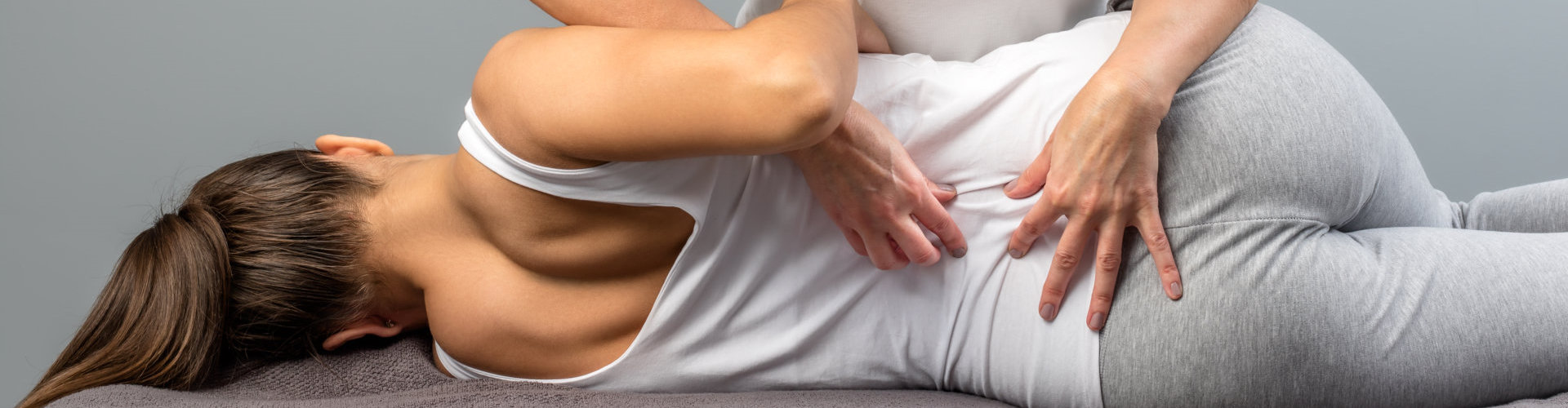 female physiotherapist doing manipulative spine treatment